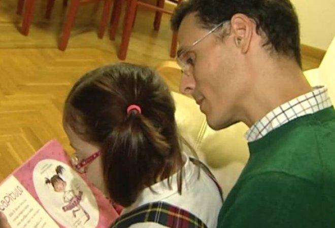 Marcos con su hija menor de síndrome de Down con habilidades sorprendentes en la lectura